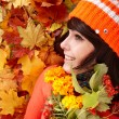 Girl in autumn orange hat, leaf group, flower. — Zdjęcie stockowe #3584413