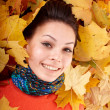 Girl in autumn orange hat on leaf group. — Stock Photo #3584420