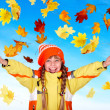 Royalty-Free Stock Photo: Child in autumn orange hat holding leaves.