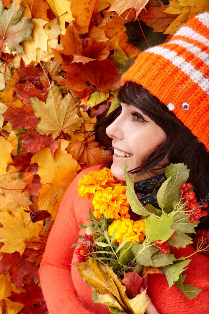  Girl in autumn orange hat on leaf group with flower.  Outdoor.  Stock Photo #3584413
