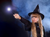 Girl in witch's hat with magic wand — Stock Photo