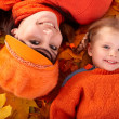 Happy family with child on autumn orange leaf. — Stock Photo