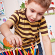 Foto Stock: Child with pencil in play room.