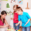 Children painting with teacher. — Stock Photo