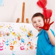 Child painting on easel by hands. — Stockfoto