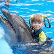 Stock Photo: Child and dolphin in blue water.
