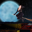 Girl witch fly over city against moon and star sky. — Stock Photo