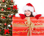 Christmas girl in santa hat and fir tree with red gift box. — Stock Photo
