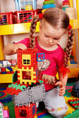 Child with puzzle, block and construction set in playroom. — Stock Photo
