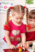 Kids mould plasticine in playroom. — Stock Photo