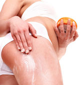 Young woman applying cosmetic cream on leg. — Stock Photo