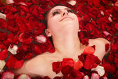 Beautiful girl in jacuzzi with rose petal. — Stock Photo