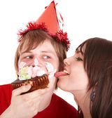 Man in party hat and girl eating cake. — Stock Photo
