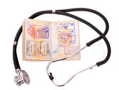 Medical still life with stethoscope and passport. — Stock Photo