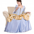 Girl in old long blue with gold dress on armchair. — Stock Photo #3915443