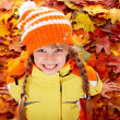 Girl in autumn orange  hat on leaf background. - Stock Photo