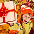 Girl in autumn orange hat on leaf and gift box. — Stock Photo