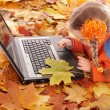Child in autumn orange leaves with laptop. — Photo