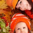 Happy family with child on autumn orange leaves. — Stock Photo #3916765