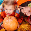 Happy family with pumpkin on autumn leaves. — Stock Photo #3916773