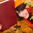 Girl in autumn orange leaves with book. - Zdjcie stockowe