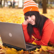 Girl in autumn orange leaves with laptop.Fall sale. — Stock Photo #3916799