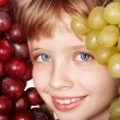 Face of child girl with grapes. — Stock Photo
