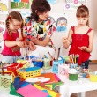 Children with teacher draw paints in playroom. — Stock Photo