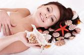 Beauty young woman holding starfish. — Stock Photo