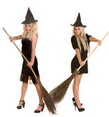 Halloween witch blond in black dress and hat on broom. — Stock Photo