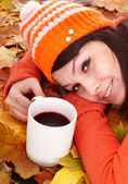 Girl in autumn orange leaves with cup coffe. — Stock Photo