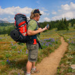 Hiker checks GPS - Stock Photo