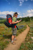 Hiker checks GPS — Stock Photo