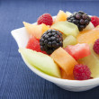 Berries and melon in a bowl on the table — Stock Photo