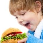 Girl eating appetizing hamburger — Stock Photo