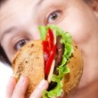 Woman eating hamburger — Stock Photo