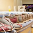 Pairs of bowling shoes lined up in shoe rack — Stock Photo