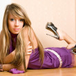 Yong woman in a violet dress lie on the floor. — Stock Photo