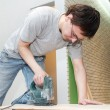 Worker cutting floor board with jigsaw - Stock Photo