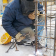 Worker welding metal lattice at construction s — Stock Photo #3244427