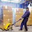 Worker with stacker at warehouse - Foto Stock