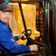 Forklift loader worker at warehouse - Stock Photo