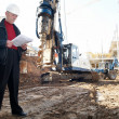 Engineer with documentation at construction site - Stock Photo
