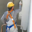 Builder facade painter at work - Stock Photo