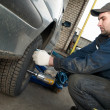 Machanic repairman at tyre replacement - Stock Photo