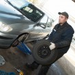 Serviceman at tyre work - Stock Photo