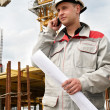 Builder at construction site with phone — Stock Photo #3247795