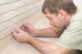 Worker tiler at wall decoration work — Stock Photo