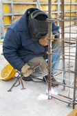 Worker welding a metal lattice at construction s — Stock Photo