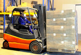 Worker and forklift loader at warehouse — Stock Photo